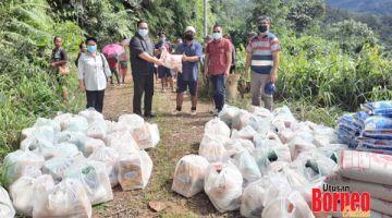 SERAH:Hendrus (dua kiri) menyerahkan bantuan bakul makanan kepada penduduk kampung, dalam tinjauannya ke perkampungan dalam DUN Tandek.