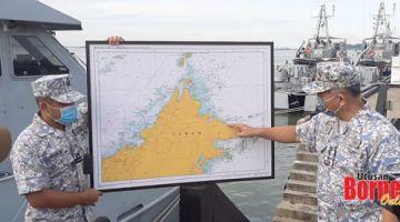 LOKASI KEJADIAN: Rusli (kanan) menunjukkan lokasi kapal kargo karam di Perairan Terumbu Segama, kira-kira 67 batu nautika dari Sandakan.
