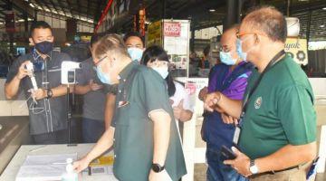 Uggah memeriksa buku pendaftaran pelanggan di Medan Selera Pasar Bandar Riyal.