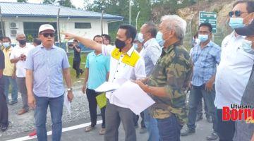 RUNTUH: Bung Moktar bersama Jafry, Limus dan James diberi penerangan mengenai jalan raya Paitan-Kinabungan yang terputus akibat tanah runtuh oleh pegawai JKR.