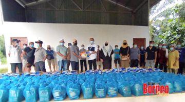 SAMPAIKAN: Ruddy (enam kiri) menyampaikan bantuan bakul makanan kepada penduduk kampung.