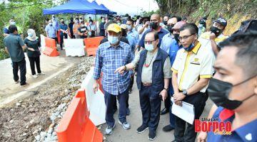 TINJAU: Hajiji bersama-sama dengan Jeffrey melihat kerja-kerja pembaikan di jalan yang rosak di KM44.7 Jalan Kota Kinabalu - Penampang - Tambunan.