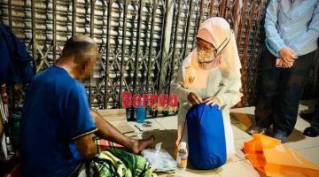 Fatimah menyampaikan bantuan kepada seorang gelandangan di sekitar pusat Bandar Raya Kuching, malam Rabu