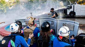 HURU-HARA: Penunjuk perasaan bertempur dengan polis selepas seorang artis jalanan                   ditembak mati di Panguipulli, Santiago pada Sabtu lepas. — Gambar AFP