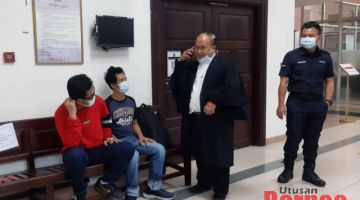 Kedua-dua tertuduh bersama peguam mereka (dua kanan) semasa berada di lobi Mahkamah Kuching.