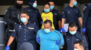 DIDAKWA: Polis melakukan kawalan ketat terhadap ibu kandung dan bapa tiri kanak-kanak lelaki yang ditemukan lemas di dalam tong air, ketika hadir bagi pertuduhan kes dera di Mahkamah Ayer Keroh semalam. — Gambar Bernama