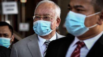DITANGGUHKAN: Najib (tengah) hadir untuk perbicaraan kes yang dihadapinya berhubung dana 1Malaysia Development Berhad (1MDB) di Mahkamah Tinggi semalam. — Gambar Bernama