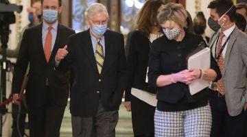 TRUMP DIBEBASKAN: Mitch McConnell (dua kiri) berjalan menuju ke pejabatnya pada akhir perbicaraan pendakwaan Trump ke atas Capitol AS di Washington, kelmarin. — Gambar AFP
