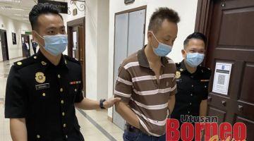 Tertuduh (tengah) diiring pegawai SPRM semasa berada di Kompleks Mahkamah Kuching.