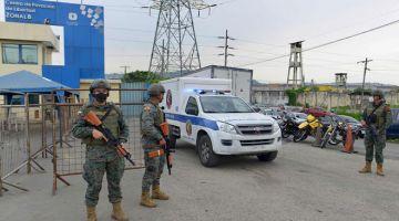 KAWAL: Anggota pasukan keselamatan berkawal ketika ambulans bergerak keluar dari Pusat Tahanan Guayaquil selepas rusuhan ganas meletus kelmarin. — Gambar AFP