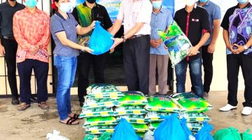 SERAH: Jonnybone (tengah) menyerahkan bantuan bakul makanan kepada penduduk di Dewan Serbaguna Daerah Telupid.