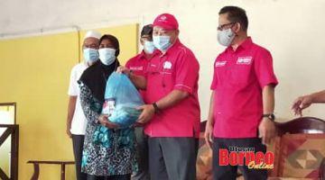 BAKUL MAKANAN: Hamsan menyampaikan bantuan bakul makanan kepada salah seorang penduduk Kampung Nunuyan sambil diperhatikan oleh Mokran.