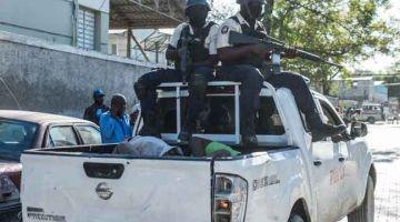 DITANGKAP SEMULA: Beberapa banduan dibawa di belakang sebuah trak kembali ke penjara Croix-des-Bouquets selepas mereka melarikan diri yang menyebabkan beberapa orang terbunuh kelmarin. — Gambar AFP