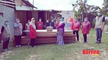 BANTU: Azizah (tiga kiri) menyampaikan sumbangan peralatan dan kelengkapan baikpulih rumah kepada salah sebuah keluarga di Kuala Penyu.