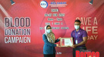 PENGHARGAAN: Miranda (kiri) menyampaikan sijil penghargaan kepada wakil dari Unit Perubatan Transfusi HQE II Dr Dinesh Parakash (kanan).