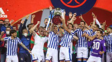 GEMBIRA: Pemain dan kru pasukan Real Sociedad meraikan kejayaan mereka di atas podium dengan menjulang trofi kejuaraan selepas menewaskan Athletic Bilbao 1-0 pada final Copa del Rey di Stadium La Cartuja, Sevilla. — Gambar AFP
