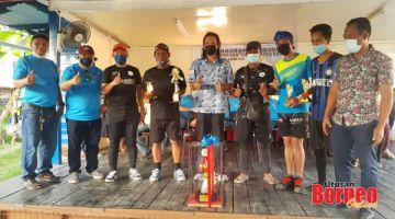 JUARA: Pasukan Rukut-Rukut yang menjuarai Pertandingan Sepak Takraw Program Rakyat Tanjung Aru bergambar bersama Mohd. Hasnol (tengah), Reduan (tiga kiri), Hamid dan Khalid selepas majlis penyampaian hadiah.