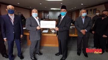 TERIMA: Rubin (dua kiri) menerima cek replika dari Ruslan, turut hadir ialah Pengurus Besar Kumpulan SEDCO Datuk Pengiran Saifuddin Pg. Tahir (kiri)