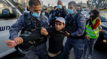 TAHAN: Anggota polis Israel menahan seorang aktivis warga Israel semasa demonstrasi di Jerusalem. — Gambar AFP