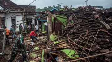 BENCANA: Askar Indonesia dan penduduk setempat memeriksa kerosakan rumah di Malang, Jawa Timur semalam, sehari selepas gegaran bermagnitud 6.7 pada skala Richter melanda wilayah berkenaan kelmarin. — Gambar AFP