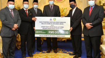 SAKSI: Tun Juhar (tiga kanan) semasa menyaksikan simbolik penyerahan bantuan Ramadan.