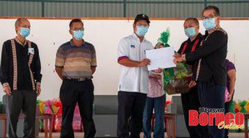 PENGHARGAAN: Ewon (tengah) menyampaikan sijil penghargaan dan hamper kepada salah seorang penerima pada majlis itu.