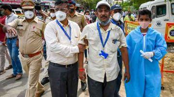 SELAMAT: Pekerja hospital mengiringi seorang pesakit (dua kanan) selepas kebakaran di unit ICU di Hospital Vijay Vallabh, di pinggir Mumbai semalam. — Gambar AFP