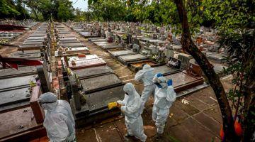 SERIUS: Gambar fail 26 Mac lalu menunjukkan para pekerja berseragam PPE bersiap sedia untuk mengebumikan mayat pesakit COVID-19 di perkuburan perbandaran Sao Joao di Porto Alegre. — Gambar AFP