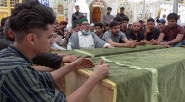 PILU: Ahli keluarga dan sanak saudara meratapi mangsa tragedi kebakaran Hospital Ibn Al-Khatib semasa perarakan pengebumian di makam Imam Ali di Najaf, kelmarin. — Gambar AFP