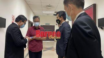 Suspek bersama peguamnya di Mahkamah Kuching, hari ini.