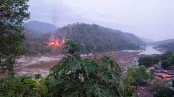 DITAWAN: Gambar serahan akhbar Kawthoolei Today semalam menunjukkan kebakaran                     di pangkalan tentera Myanmar di tepi sungai Salween, seperti yang dilihat dari bandar Mae Sam Laep di wilayah Mae Hong Son Thailand, selepas pangkalan itu diserang dan ditawan oleh pemberontak KNU.  — Gambar AFP