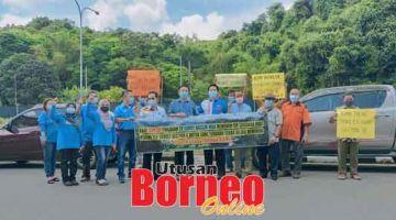 MANTAH: Dennis (mua, empat kanan), Roland (lima kanan), Dr Teo (enam kanan) enggau kaban PKR ke bukai, mandangka banner enda setuju enggau peminta Garry minta nyukat tanah peranak di Long Terawan.