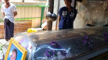 SAYU: Ahli keluarga memandang sayu pada keranda Zaw Shine, pemilik gerai teh, yang maut selepas ditembak di dada di tengah-tengah ketegangan antara penunjuk perasaan dan anggota pasukan keselamatan di Mandalay, kelmarin. — Gambar AFP