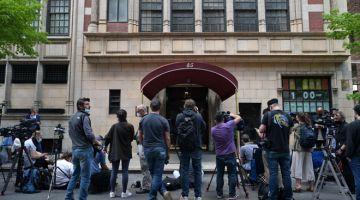GELEDAH: Anggota media berhimpun di luar sebuah bangunan ketika para penyiasat menggeledah kediaman Giuliani di New York kelmarin. — Gambar AFP