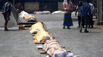 RITUAL TERAKHIR: Mayat beberapa pesakit COVID-19 dilihat di sebuah kawasan pembakaran mayat di New Delhi, kelmarin. — Gambar AFP