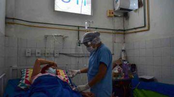 RAWAT: Gambar fail menunjukkan pekerja perubatan merawat pesakit COVID-19 di unit rawatan rapi di Hospital Awam Sao Bento di Abaetetuba, Brazil pada 23 April lalu. — Gambar AFP