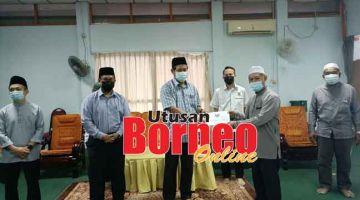KENA MEMANAH: Dr Abdul Rahman (tiga kiba) nyuaka geran nya ngagai Penghulu JAmil Bakar seraya dikemataka Abdul Rahim (kiba), Denney, Superi enggau Penghulu Ahmad Bini (kanan).