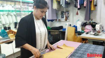 UKUR: Siti menyiapkan ukuran baju yang ditempah pelanggan di kedainya.