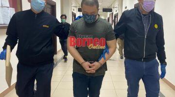 Tertuduh (tengah) diiring pegawai SPRM semasa berada di lobi Mahkamah Kuching.