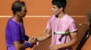 SEMANGAT KESUKANAN: Nadal (kiri) berjabat tangan dengan Alcaraz selepas tamat perlawanan di antara mereka dalam Kejohanan Terbuka Madrid di Caja Magica. — Gambar AFP