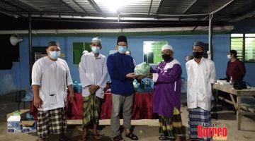 SUMBANGAN: Abu Bakar (tengah) menyerahkan barangan moreh dan kurma kepada pihak Masjid Al-Furqan Kampung Sinar Jaya.