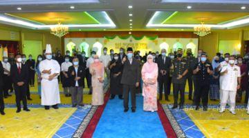 TERBAIK: Tun Juhar (tengah, depan) menunjukkan isyarat terbaik ketika merakam gambar bersama rombongan penyumbang kek hari raya.