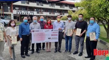 KENANGAN: Foo (empat kiri) menyerahkan replika cek bernilai RM11,100 kepada Mak sambil disaksikan Wang (enam kanan) serta tetamu kehormat yang lain.