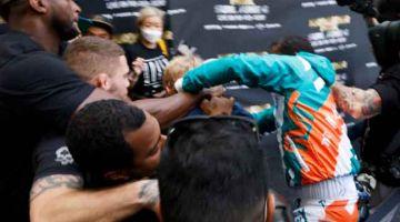 RASAKAN: Mayweather (kanan) bergelut dengan adik Logan, Jake selepas insiden merampas topi pada sidang media di Stadium Hard Rock di Miami Gardens, Florida. — Gambar AFP