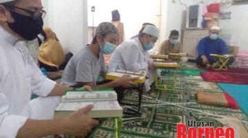 KHUSYUK: Para peserta ketika membaca surah al-Quran pada majlis itu.