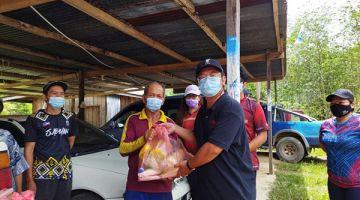 PRIHATIN: Ewon (kanan) menyampaikan sumbangan kepada seorang penerima