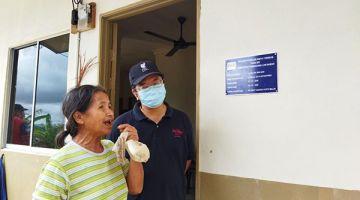 GEMBIRA: Seorang penduduk yang gembira menerima rumah PPRT, turut kelihatan Ewon (kanan)