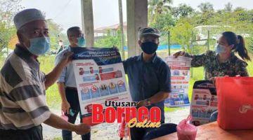MAKLUMAT PENTING: Paulus (tiga kiri) menyerahkan risalah kepada Ketua Kampung Medait Basuni Sidop disaksikan Mahathir (dua kiri) dan Linda (kanan).