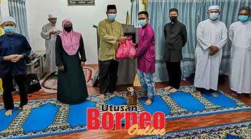 SANTUNI ASNAF: Dr Abdul Rahman (empat kiri) menyerahkan sumbangan kepada salah seorang penerima. Turut kelihatan Abdul Rahim (kiri), Leah (tiga kiri) Superi (tiga kanan) serta yang lain.