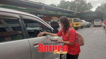 AGIHKAN: Suzanne menyampaikan bubur lambuk kepada salah seorang pemandu ketika aktiviti di Luak Bay kelmarin.